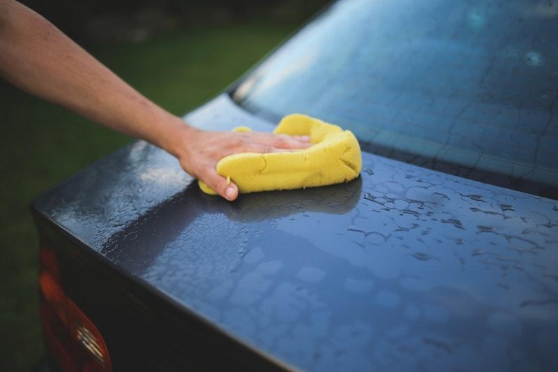 Homem limpando a superfície do carro