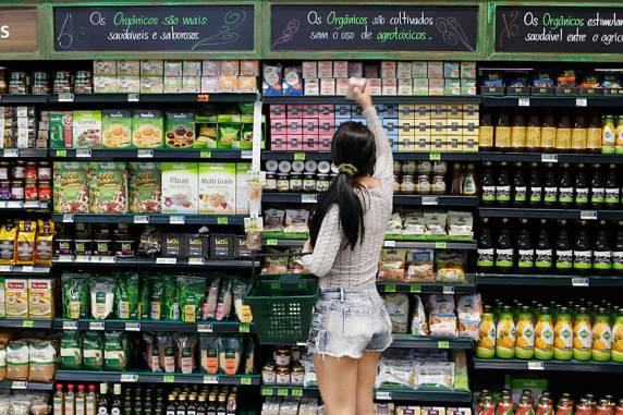 Merchandising no PDV: mulher escolhendo produto em gôndola decorada