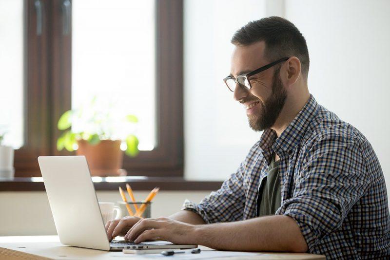 Homem fazendo mexendo no computador.