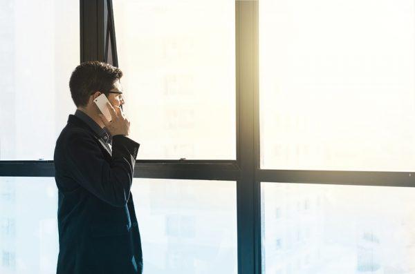 Atendimento no atacado online, um homem de terno fala ao telefone em frente a uma janela