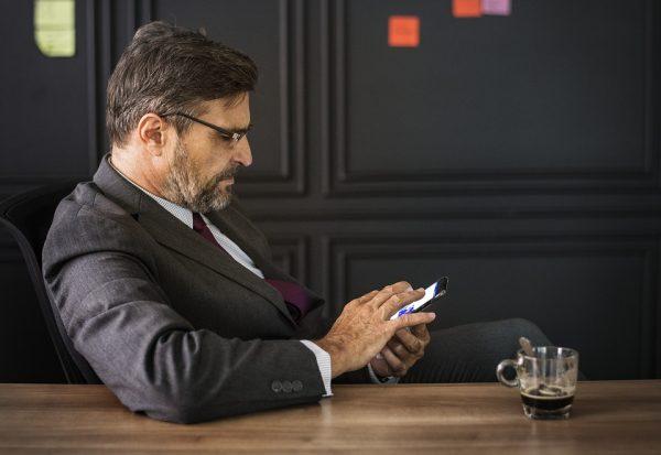 Homem de terno sento em mesa usando o celular para atendimento no atacado online