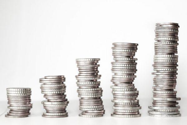 Pilhas de moedas em tamanho crescente enfileiradas, indicando o cashback do Martins.