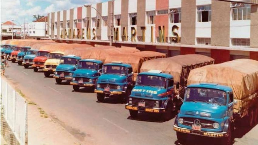 A logística do Martins nos anos 80. Caminhões azuis estacionados na porta dos Armazéns Martins.