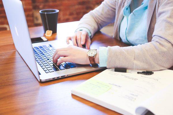 Close em mãos femininas digitando em um computador. Ao lado um livro, do outro uma caneca de café. Ela trabalha em um sistema de gestão para o varejo.