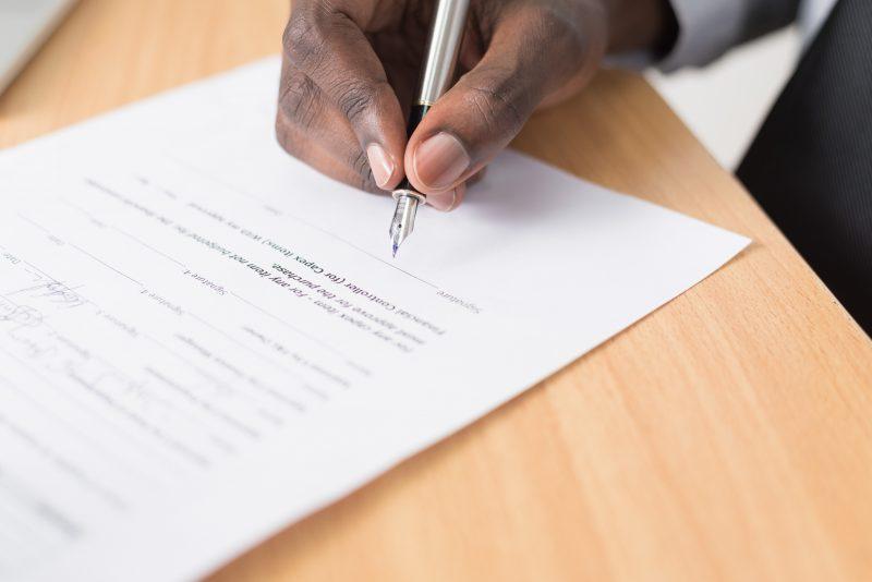 abrir um mercadinho de bairro: mão com caneta assina um documento