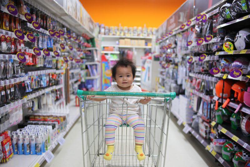 abrir um mercadinho de bairro: bebê sentado em carrinho no corredor de supermercado