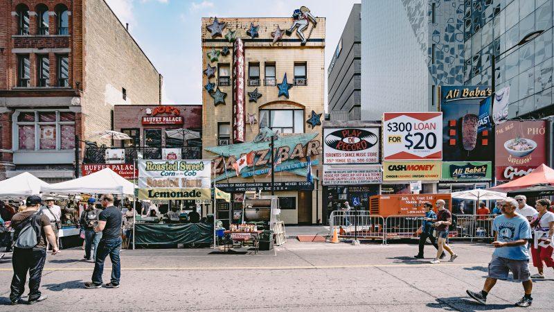Abrir um mercadinho de bairro: rua movimentada com várias lojas