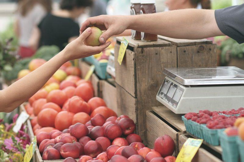 Pessoa entrega uma maçã a outra em banca de frutas. Fidelizar clientes no varejo.