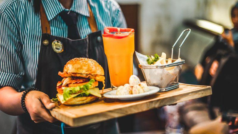 Gestão de bares e restaurantes: garçom carregando hamburguer, suco e acompanhamentos