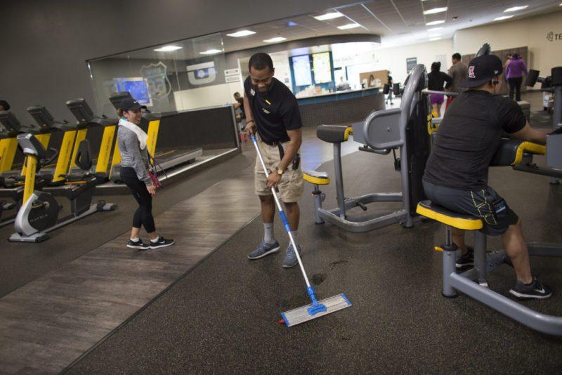 Homem limpando o chão de academia