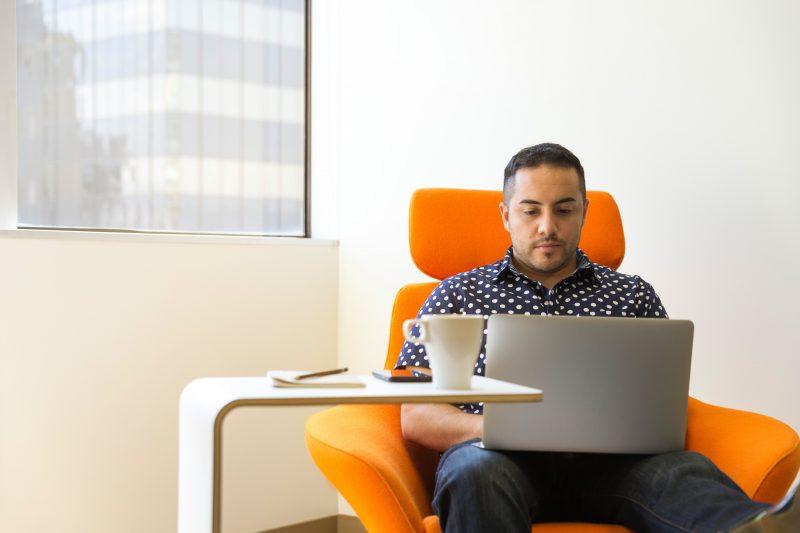 representante de vendas martins: homem sentado em cadeira laranja com notebook