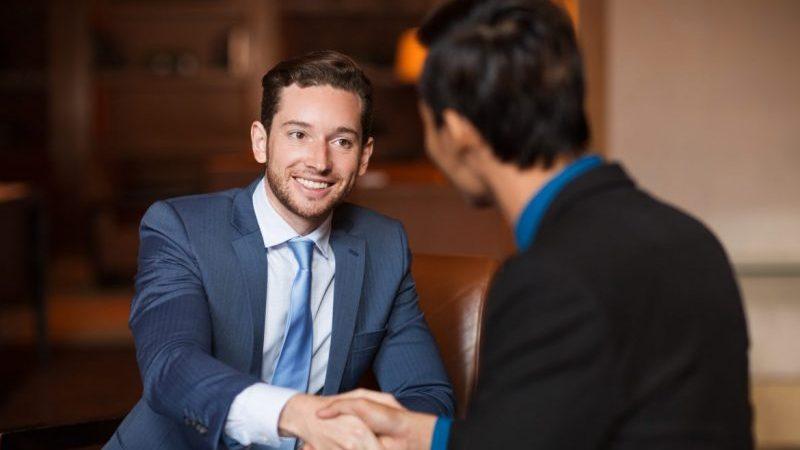 acalmar o cliente nervoso: homem sorridente de terno aperta a mão de outro, que está de costas