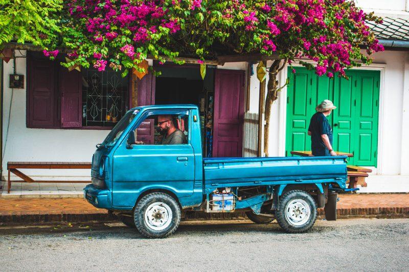 como montar delivery: caminhoneta azul em rua em frente à árvore florida