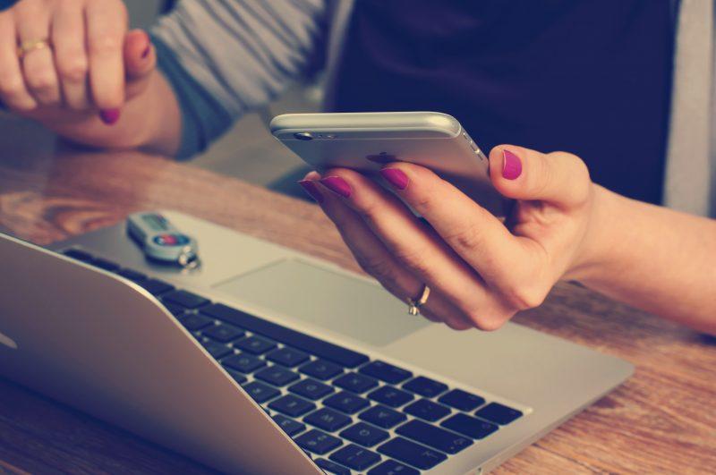 comprar com segurança: pessoa segura smarphone, macbook em cima da mesa