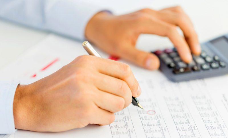 estratégias de vendas no varejo: pessoa calculando em calculadora e escrevendo em papel