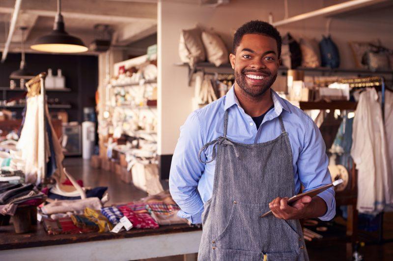 estratégias de vendas no varejo: rapaz de avental em loja de roupas