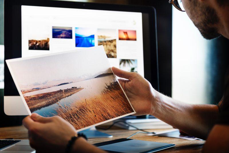 impressora tanque de tinta: pessoa segura foto em frente à tela.