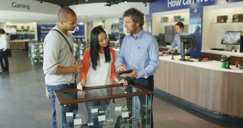 loja física ou virtual: vendedor mostra eletrônico para casal em loja