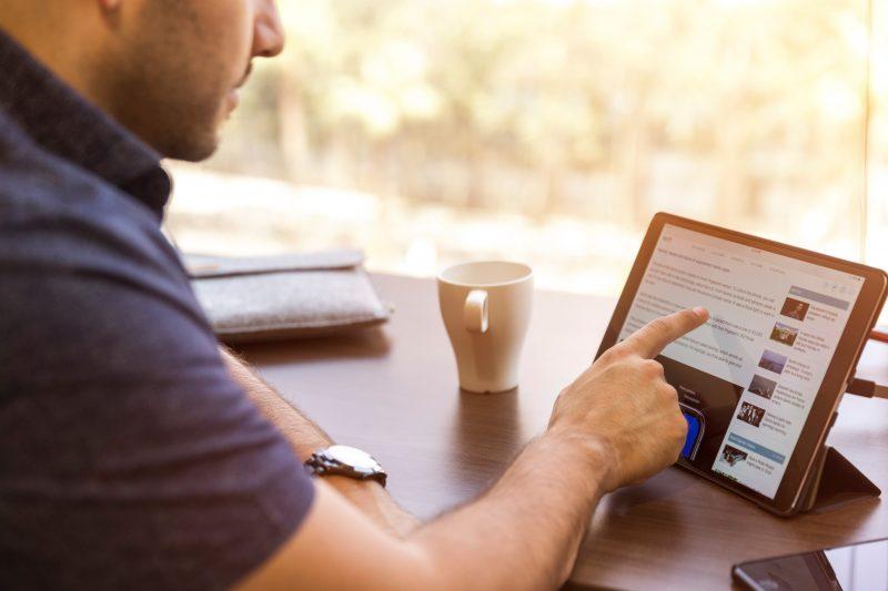 loja física ou virtual: homem trabalha em tablet sobre uma mesa
