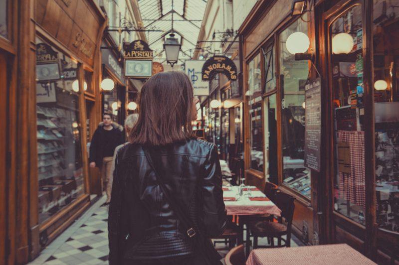 loja física ou virtual: mulher em corredor com lojas e restaurantes
