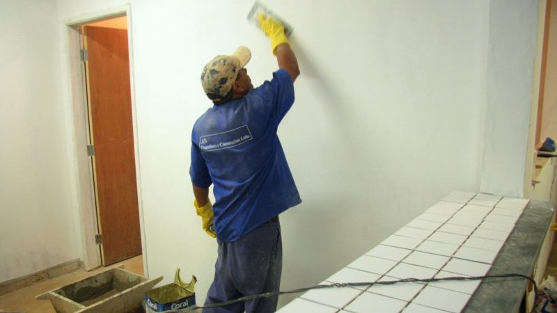 reformar a loja: pedreiro passando massa corrida em parede atrás de balcão