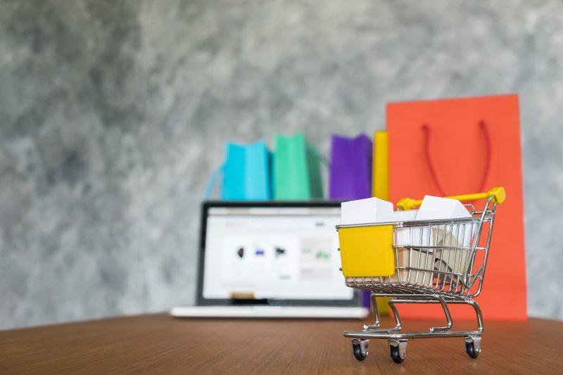 Promoção na loja: mesa com compras, carrinho e laptop com e-commerce