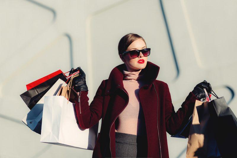 promoção na loja: mulher de óculos escuros carregando várias sacolas