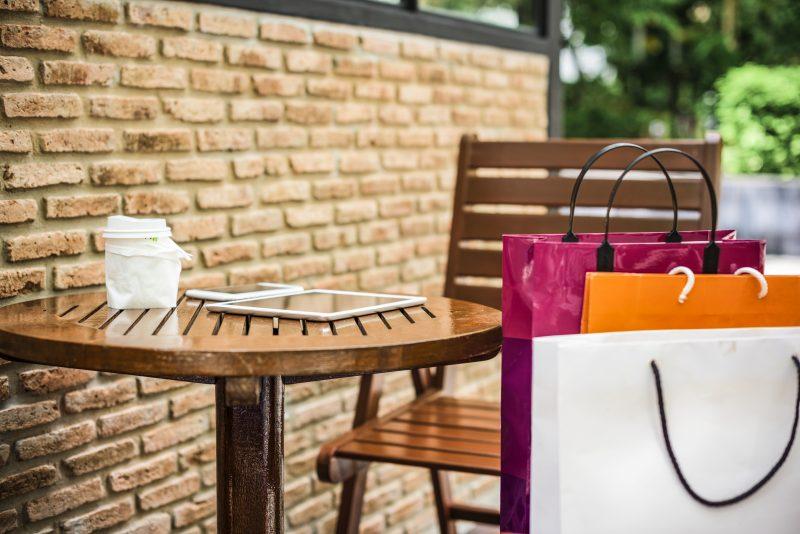 Promoção na loja: mesa com café e sacolas de compras na cadeira