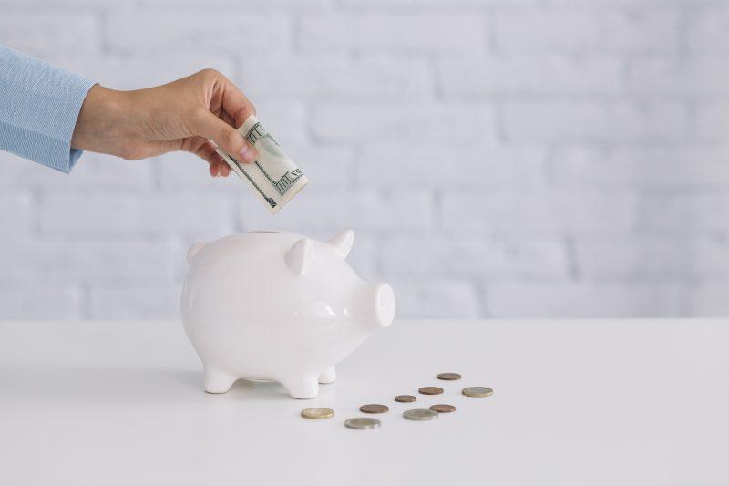 como abrir negócio com pouco dinheiro: pessoa colocando dinheiro em cofre branco