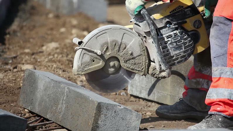 mix de materiais de construção: serra circular cortando concreto