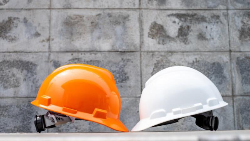 Em um fundo de parede de cimento, há dois capacetes de segurança, sendo um laranja e outro branco.