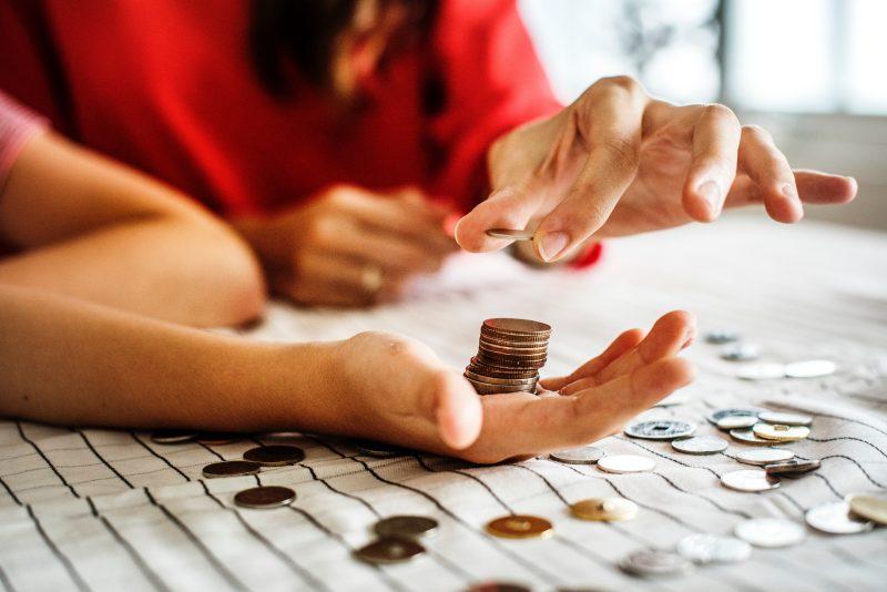Como economizar na loja? Pessoas contando moedas em cima de lençol.