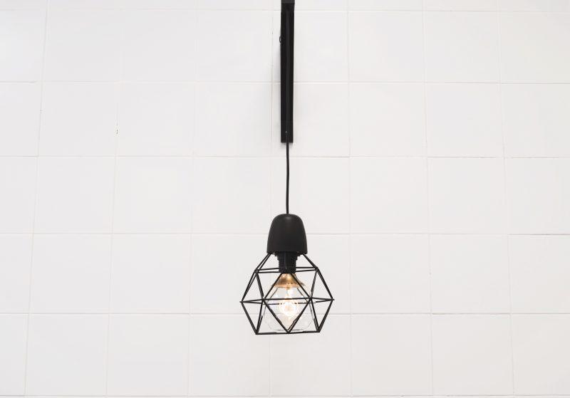 Como economizar na loja? Lâmpada em moldura preta geométrica em frente à parede branca.