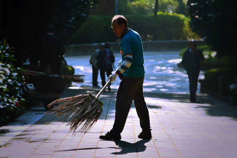 Como economizar na loja? Homem varrendo calçada com vassoura de folhas.