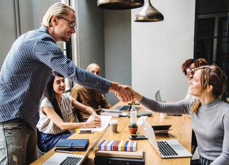 Como economizar na loja? Pessoas em reunião, aperto de mãos.