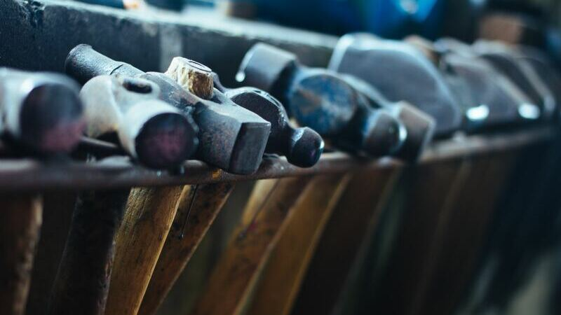 Vários martelos com cabo marrom e cabeça de ferro, organizados um ao lado do outro.