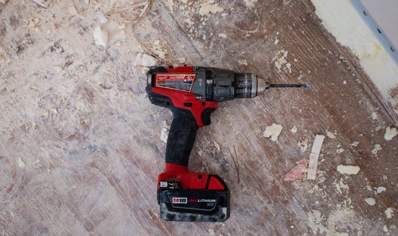 mix de materiais de construção: furadeira elétrica em superfície de madeira