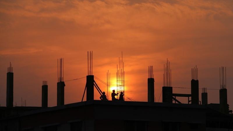 Ao pôr do sol, há duas pessoas construindo um empreendimento com arames de ferro estrutural em evidência.
