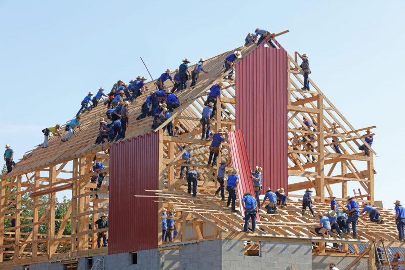 Homens erguendo um prédio: o seu mix de materiais de construção pode servir para conquistar clientes.