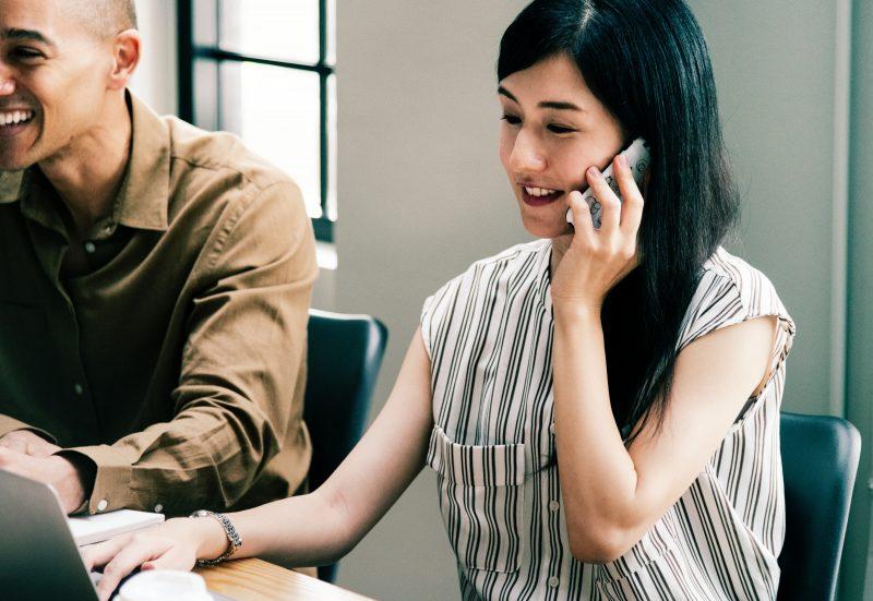 Experiência de compra: mulher fala ao celular enquanto olha para computador.