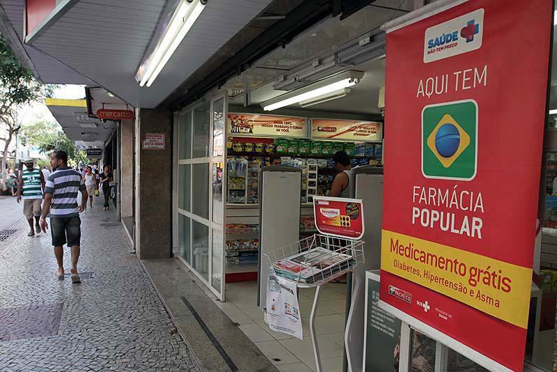 """Banner """"aqui tem farmácia popular"""" em frente à loja."""