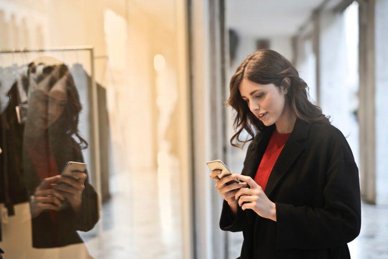 futuro do varejo: mulher olha no celular perto de roupas em loja