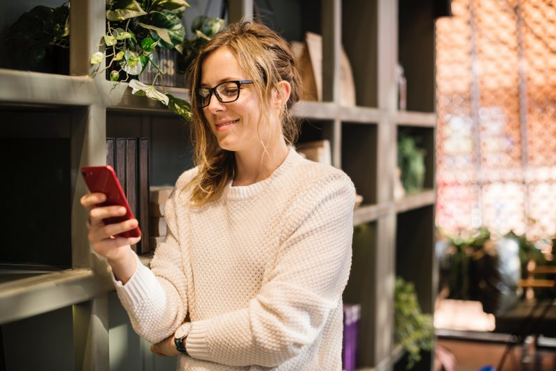 Como cuidar das redes sociais: mulher sorrindo ao mexer no celular