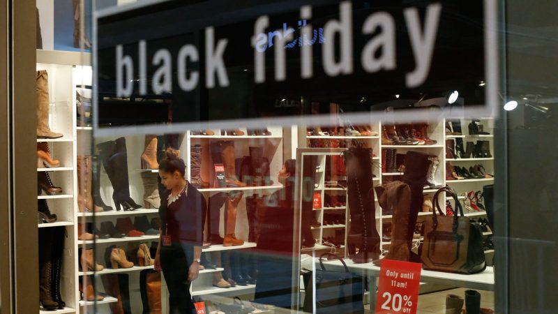 """Porta de loja com letreiro dizendo """"Black Friday"""". Uma mulher escolhe produtos."""