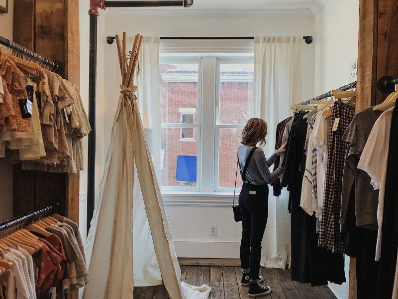 mulher olha roupas em loja. Experiência de compra.