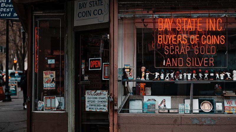 Vitrine de lojas de penhores com itens antigos dispostos para venda e letreiro de neon indicando os produtos que compra.