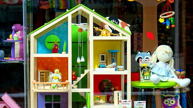 Vitrine de loja de brinquedos com bonecas, casinha de bonecas e outros itens.