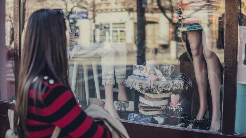 Cena de visual merchandising bem construída, vitrine com livros combinando com manequins vestidos com roupas da loja.