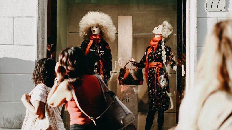 Mulheres observam vitrines com manequins vestidas com roupas pretas e vermelhas.
