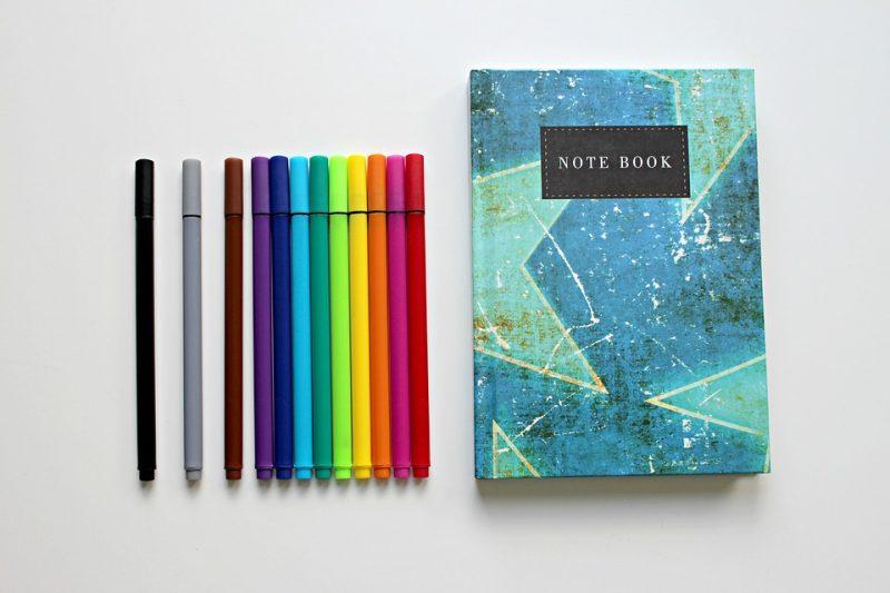 Feriados e pontos facultativos: caderno de anotação com canetas coloridas